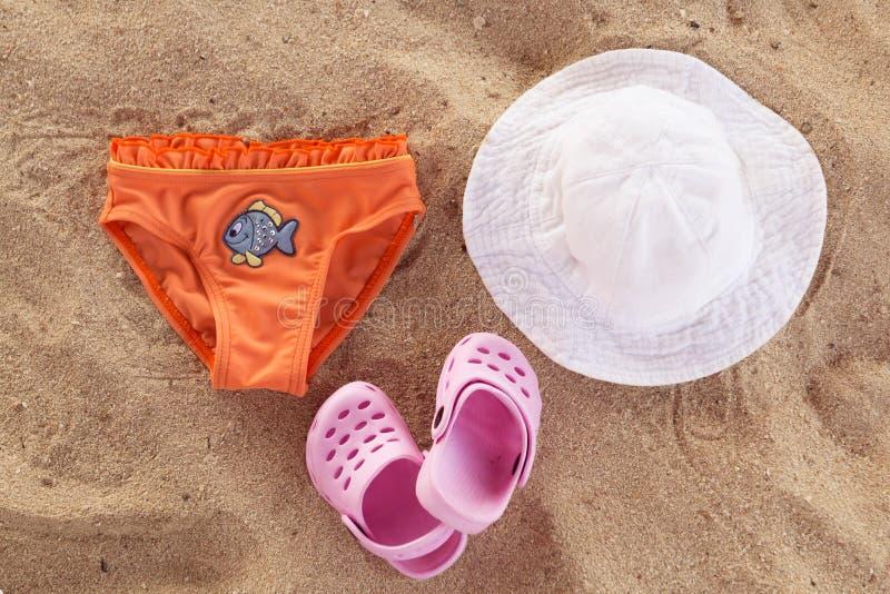 Beachwear лета младенца, розовые темповые сальто сальто, белая шляпа, оранжевые трусы с голубыми рыбами на пляже песка Принципиал стоковые фотографии rf