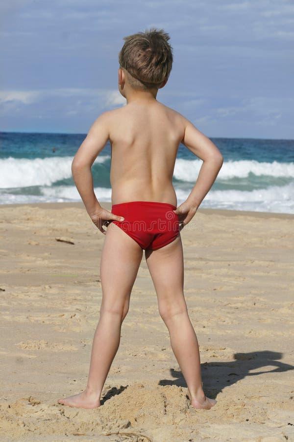 Beachy Days 2. A boy (facing away) at the beach stock image