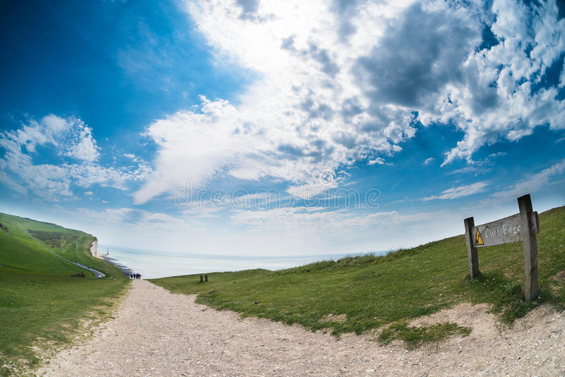 Beachy Head Cliff Edge fisheye. Cliff Edge danger sign on Beachy Head trail during a sunny day with nobody - stunning clouds and blue sky - UK (05/2016 stock photo
