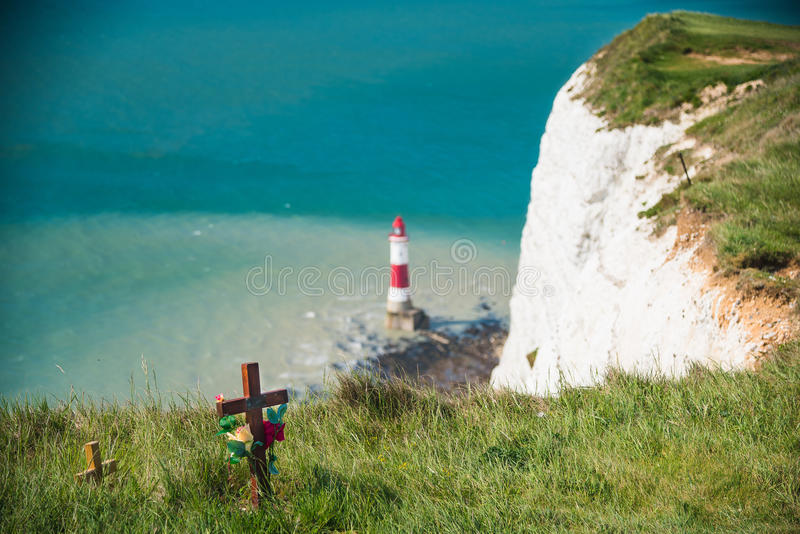Beachy Head Lighthouse Suicide. Deadly suicide cliffs with cross and Beachy Head Lighthouse in the background - sadness, depression - UK (05/2016 royalty free stock photo