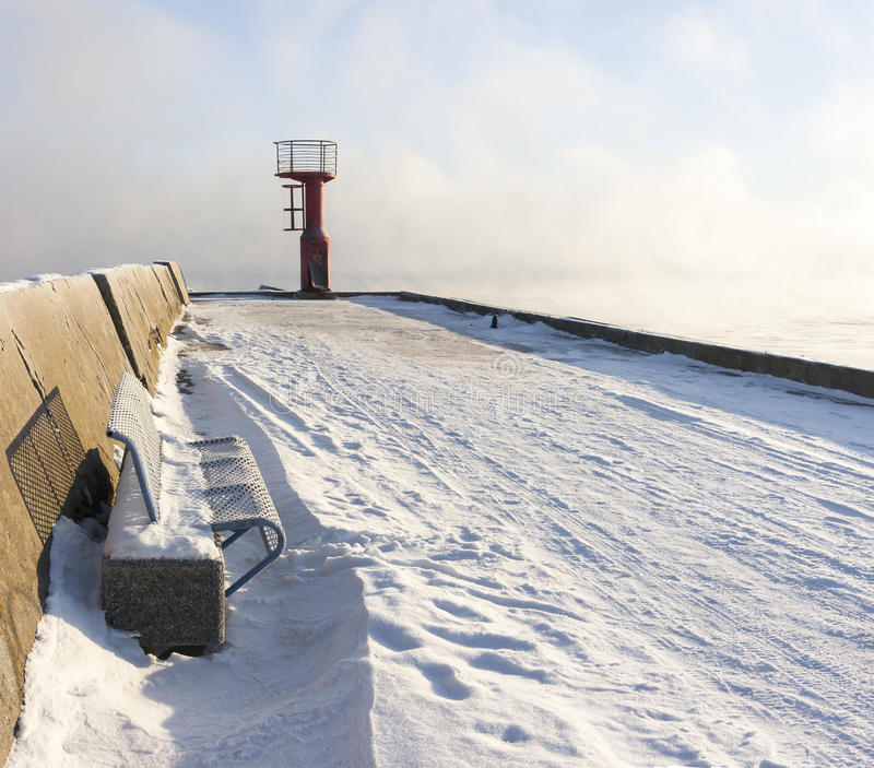 Beacon and bench on snowy mole stock image