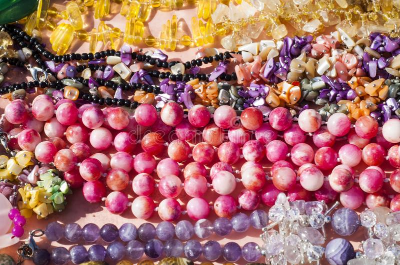 Bead, chaplet, beading. A small piece of glass, stone, or similar material, typically rounded and perforated for threading with others as a necklace stock photos