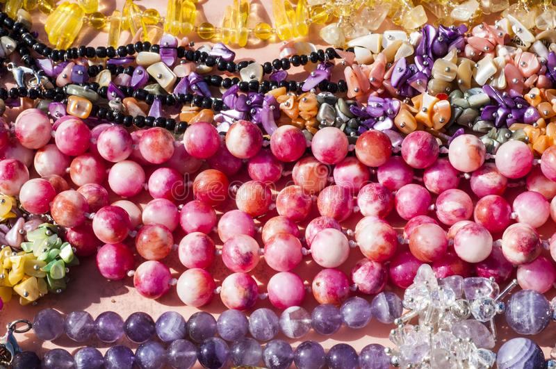 Bead, chaplet, beading. A small piece of glass, stone, or similar material, typically rounded and perforated for threading with others as a necklace royalty free stock images