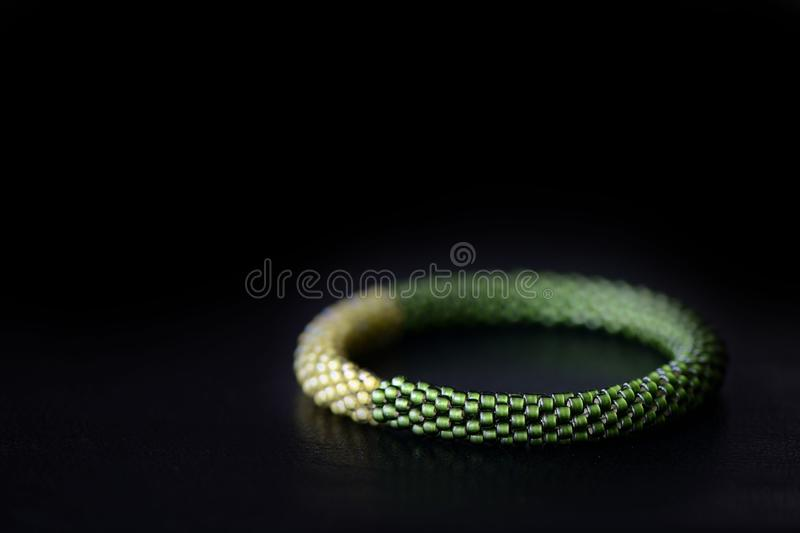 Bead crochet bracelet two shades of green on a dark background. Close up royalty free stock image