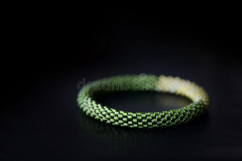 Bead crochet bracelet two shades of green on a dark background. Close up royalty free stock images