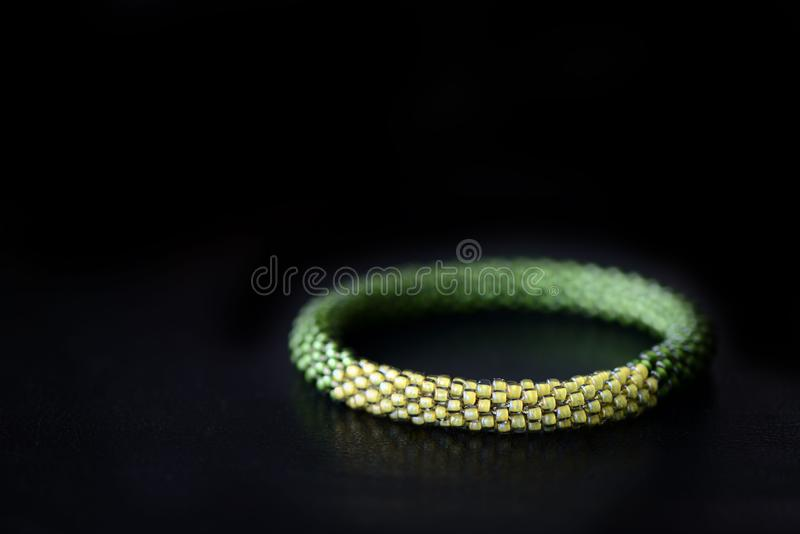 Bead crochet bracelet two shades of green on a dark background. Close up stock photos