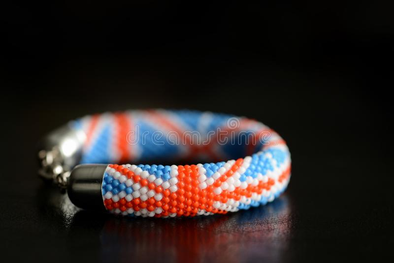 Bead crochet bracelet with United Kingdom flag on a dark background stock photography
