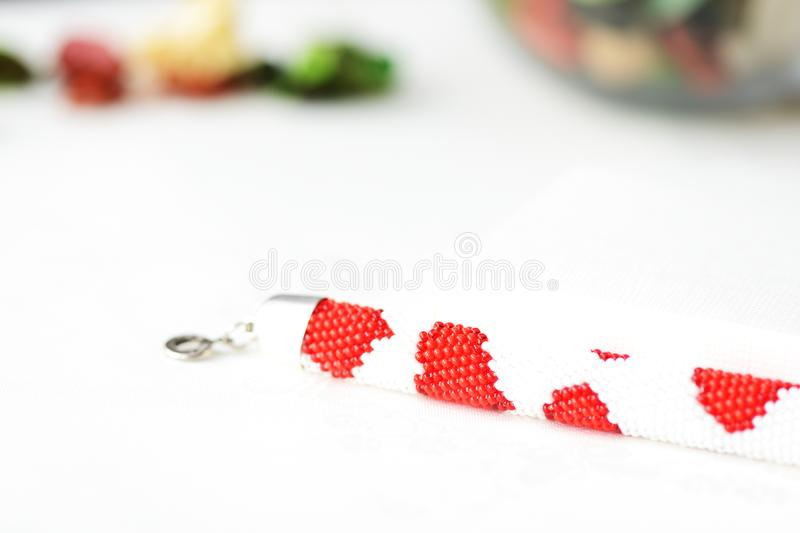 Bead crochet bracelet white color with red hearts print royalty free stock photo