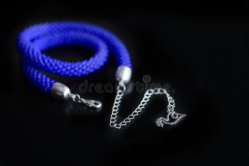Bead crochet necklace blue color a dark surfce close up. Fashion background royalty free stock image