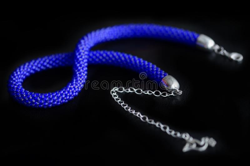 Bead crochet necklace blue color a dark surfce close up. Fashion background stock image