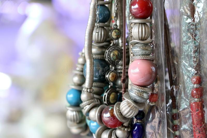 Bead necklace or rosary, threading from a rounded small piece of stone and silver material. Hang a lot to sell as souvenirs stock image