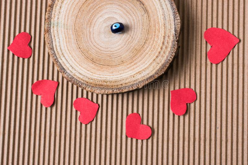 Bead on Piece of log with red paper hearts. On cardboard royalty free stock image