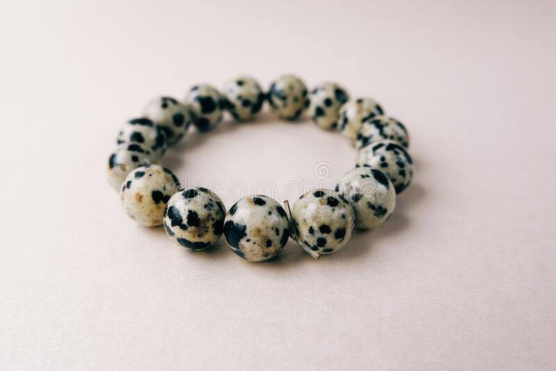 Bead stringing hand bracelet decoration. Hand made gem stone dalmatian jasper fashion accessory. stock photos
