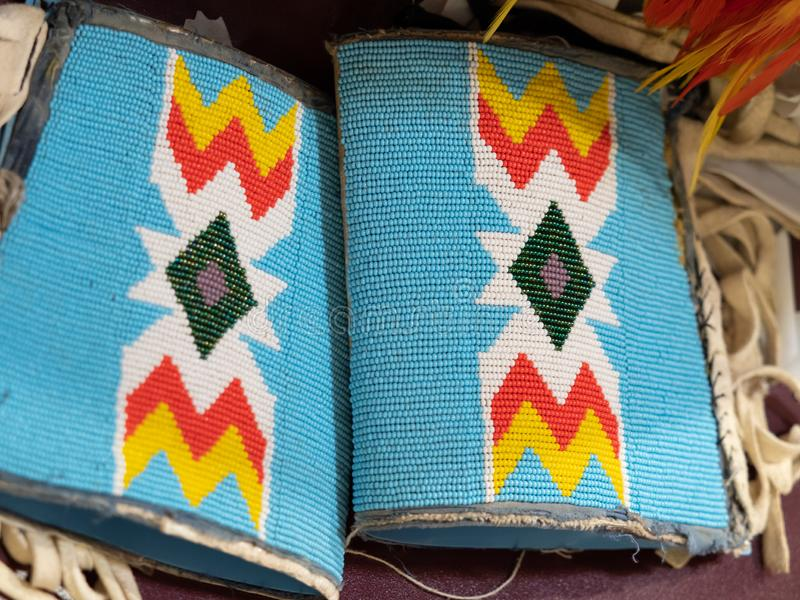Beaded Cuffs Worn at a Pow Wow. Close up of beaded cuffs worn at a pow wow with geometric pattern on light turquoise with leather fringe royalty free stock photos