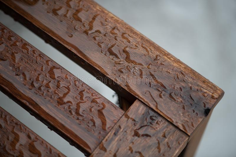 Rain on a teak bench. Beaded rain water on an oiled teak wood bench with blurred gray background royalty free stock photography