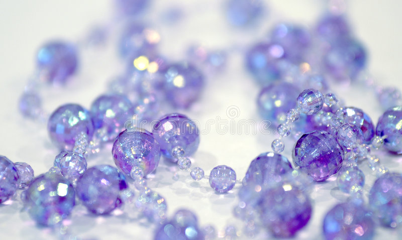 Beads. Sparkling beads in purples and blues royalty free stock images