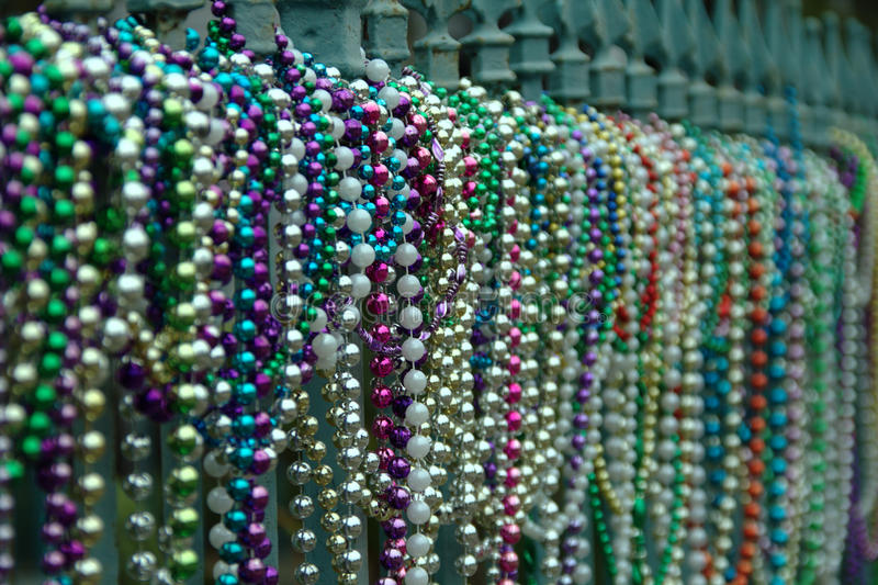 Beads aligned on fence in New Orleans in Lousiana after Mardi Gras. Alignment of multiple colored beads on a fence in New Orleans in Louisiana after the Mardi stock image