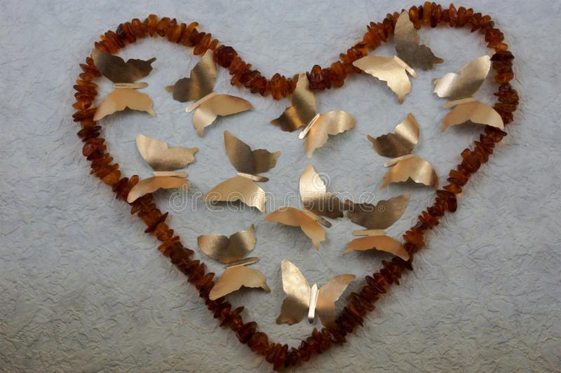 Beads of amber in the form of a heart and gold butterflies stock image