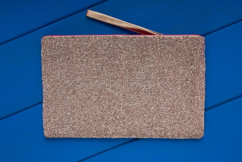 Beads handbag is on blue background, beige beautiful clutch is o royalty free stock photos