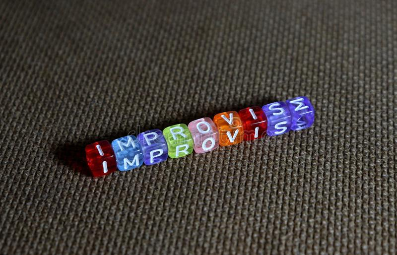 Beads Spelling `improvise` With `E` Replaced By `M`. Colourful plastic beads spelling out the word `improvise` but with the letter `E` replaced by the letter `M royalty free stock photos