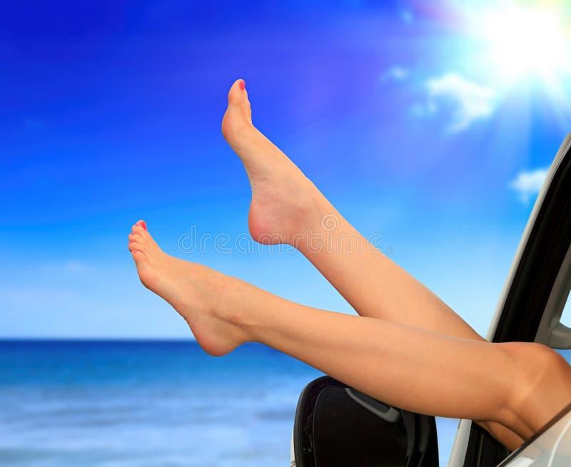 Beaitiful vrouwelijke benen tegen het overzees en de zomer de blauwe hemel Vakantie, de vakantieconcept van de reiszomer De vrouw royalty-vrije stock fotografie