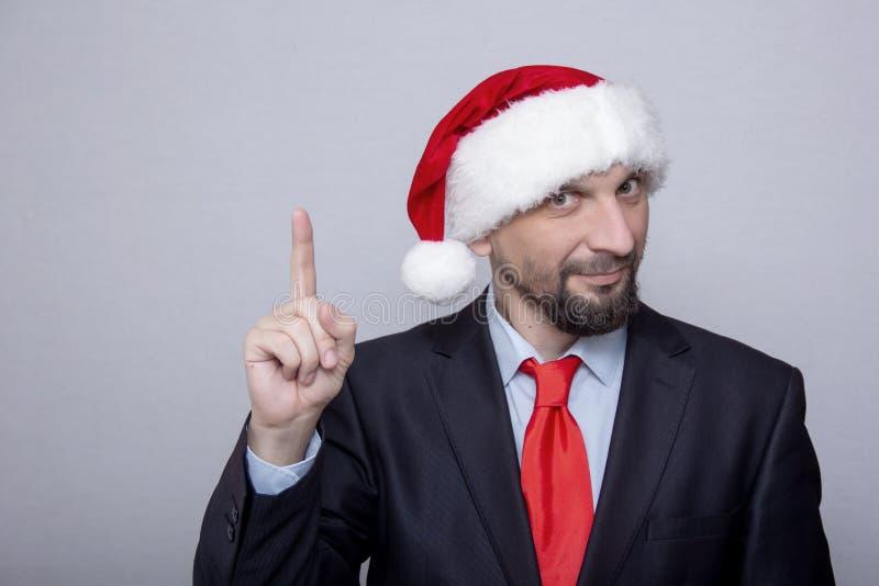 Beambte in de hoedenpunten van de Kerstman met zijn hand royalty-vrije stock foto's