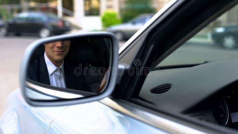 Beambte die in vleugelspiegel glimlachen van auto, het zekere zakenman drijven stock afbeeldingen