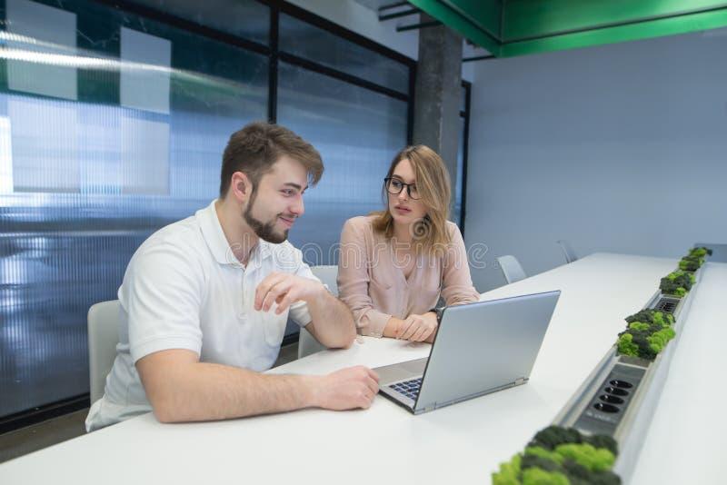 Beambten die bij een bureau dichtbij laptop en het spreken zitten de jongeren werkt bij een computer in een modern bureau royalty-vrije stock afbeelding