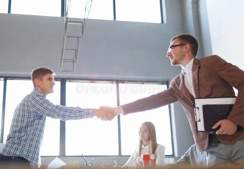 Beambten die handen op een lichte achtergrond schudden Succesvolle commerciële vergadering Communicatie concept royalty-vrije stock foto