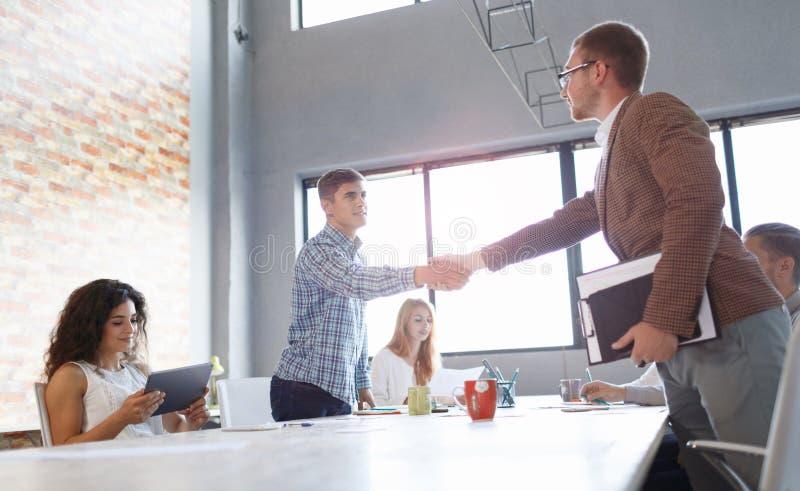Beambten die handen op een lichte achtergrond schudden Succesvolle commerciële vergadering Communicatie concept stock foto's