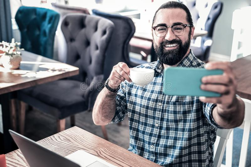 Beaming bearded man feeling relaxed making selfie and drinking coffee stock photos
