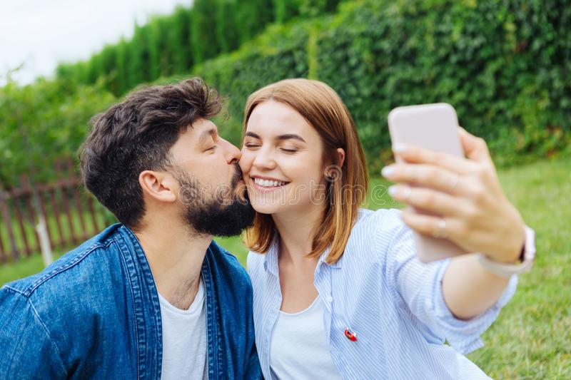 Beaming blonde-haired woman making selfie with her man. Selfie with man. Beaming blonde-haired women feeling extremely happy while making selfie with her man royalty free stock photography