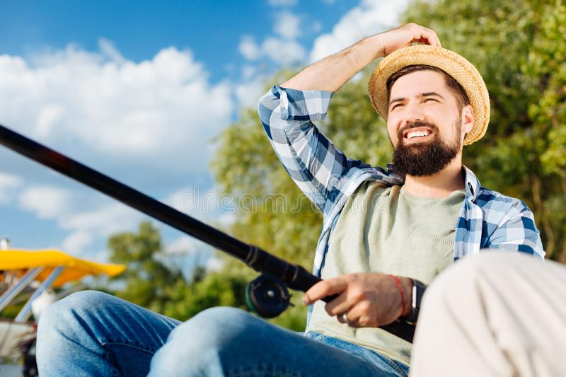 Beaming businessman feeling happy while fishing with dad royalty free stock images