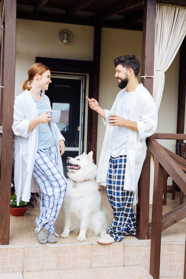 Beaming couple wearing bathrobes standing on porch in the morning royalty free stock photography