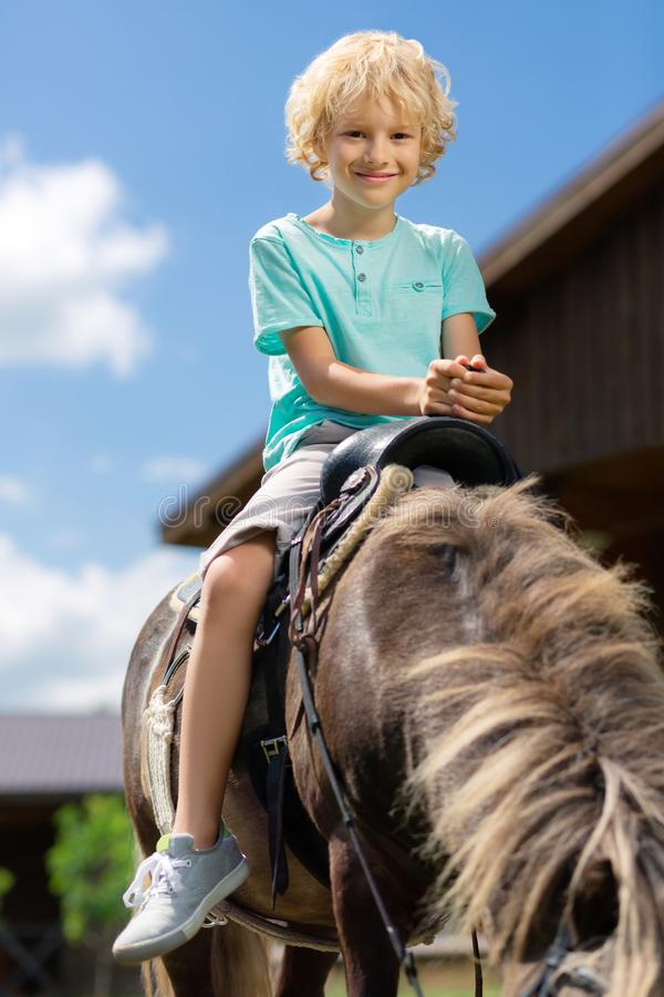 Beaming curly blonde-haired boy feeling amazing riding horse royalty free stock photo