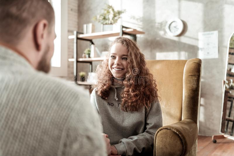 Beaming curly dark-haired client of counselor smiling broadly. Beaming client. Beaming curly dark-haired client of counselor smiling broadly after amazing stock images