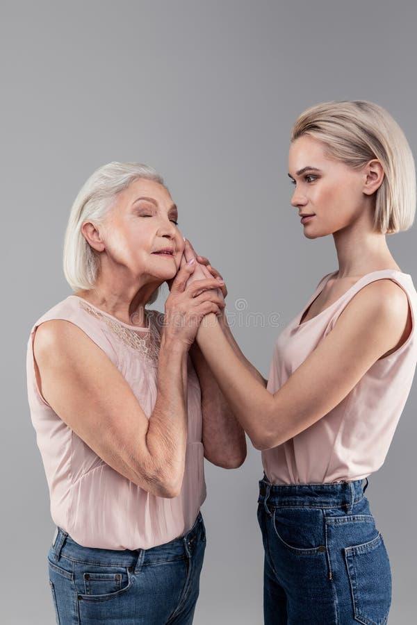 Emotional short-haired senior woman petting beautiful daughter royalty free stock image