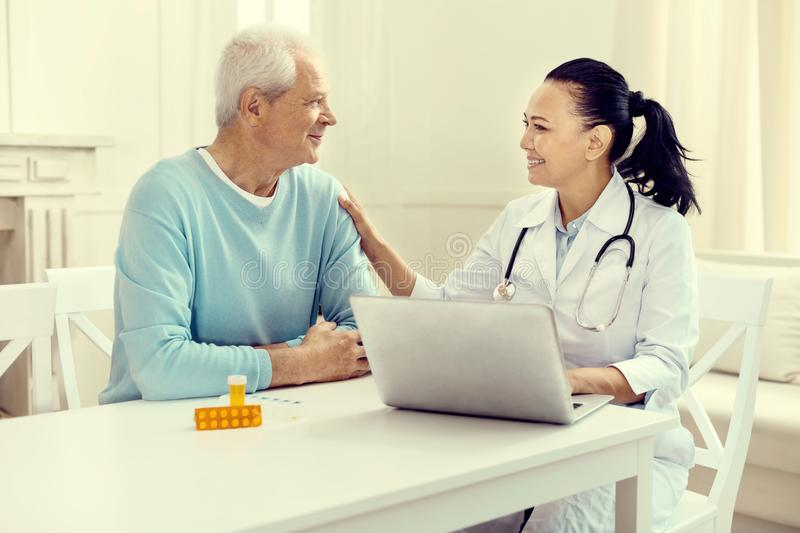 Beaming doctor smiling to senior patient stock image