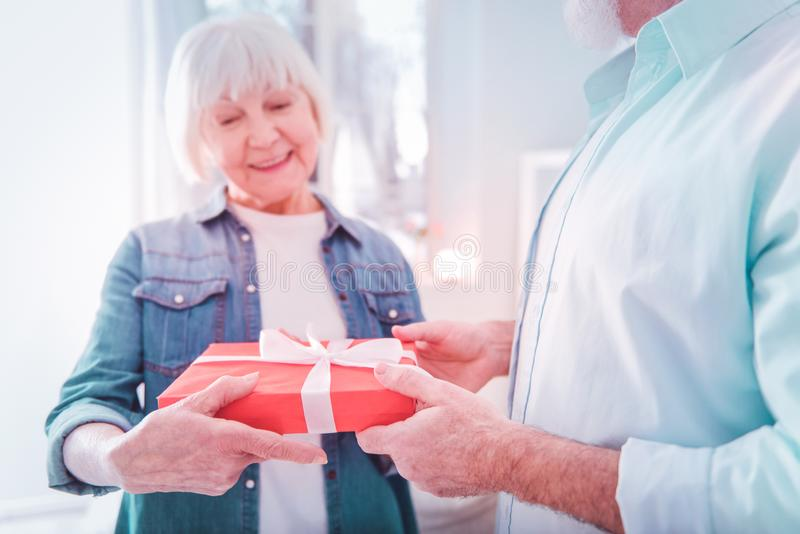 Beaming elderly lady wearing denim shirt receiving present box royalty free stock photos