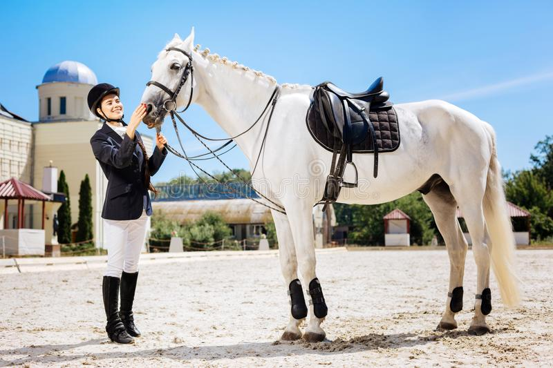 Beaming female rider getting ready for important contest stock photography