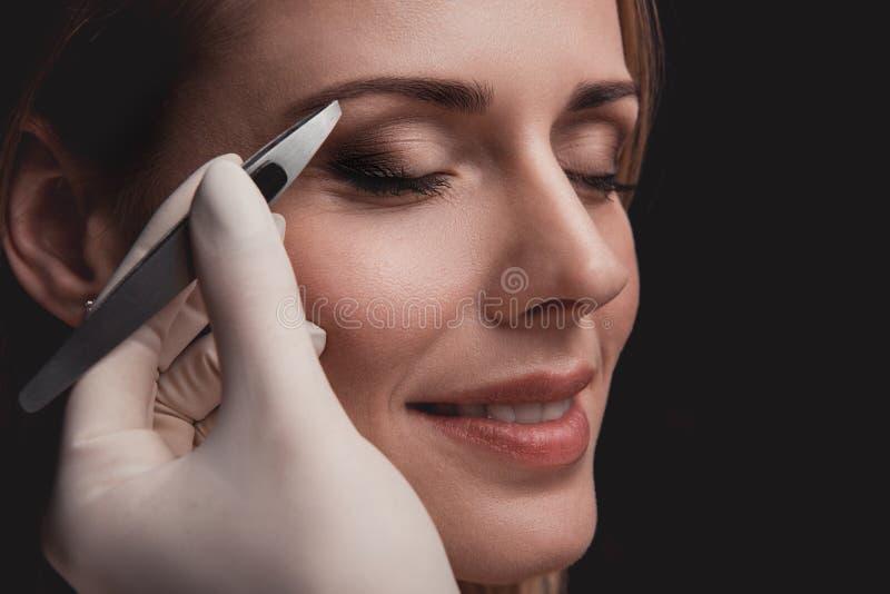 Beaming female visitor having pluck eyebrows royalty free stock image