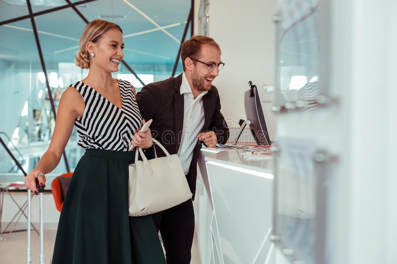 Beaming good-looking couple staying on the reception desk royalty free stock photos