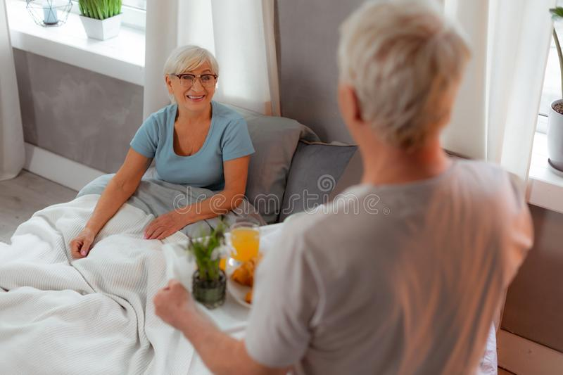 Beaming good-looking old female lying in the bed royalty free stock photography