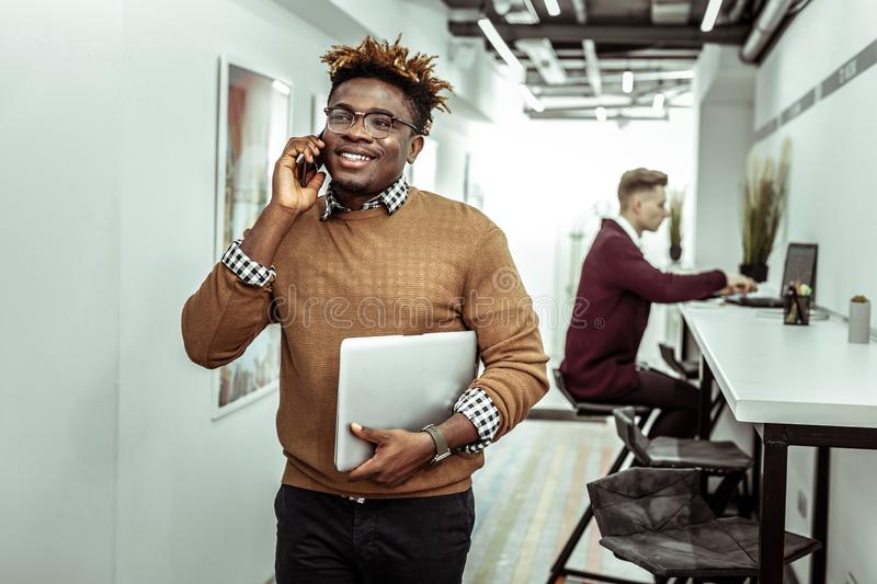 Beaming guy in clear glasses with dreadlocks having conversation on smartphone stock photo