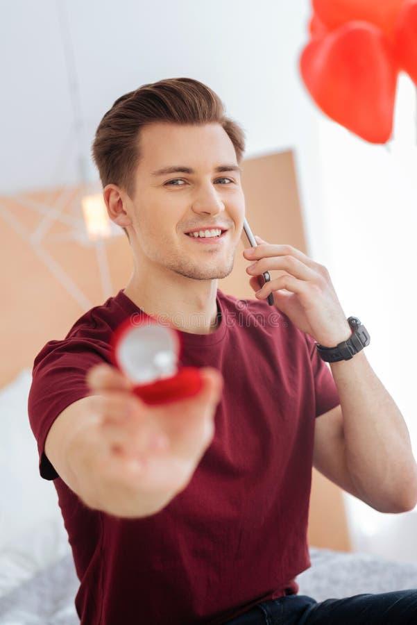 Beaming Guy Showing Proposal Ring During Phone Conversation Stock
