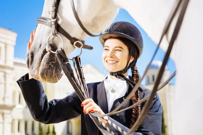 Beaming dark-haired horsewoman petting her white horse. Beaming horsewoman. Beaming dark-haired horsewoman with long fishtail petting her white horse royalty free stock images