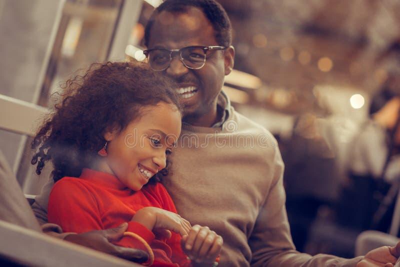Happy beaming man hugging and kissing his daughter stock photos