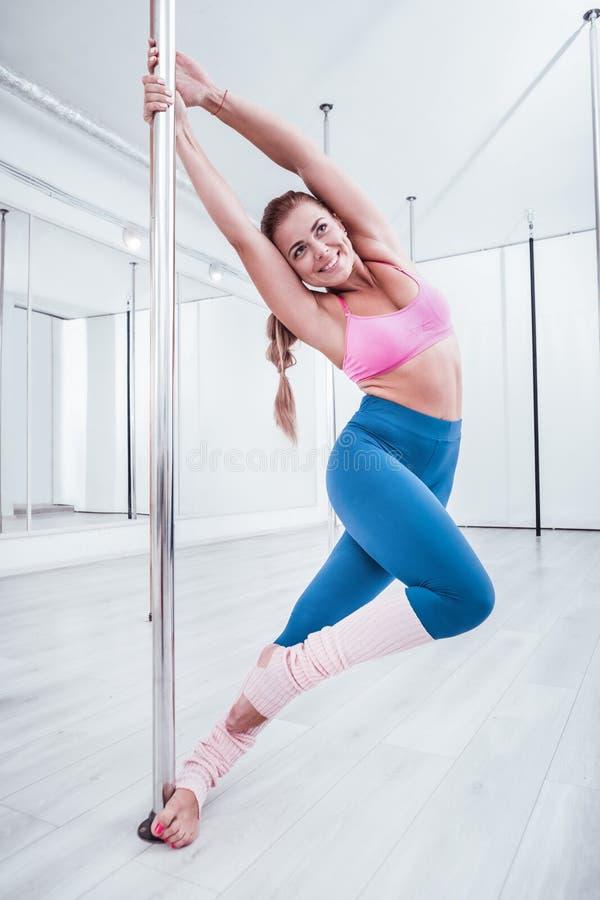 Beaming positive pole dancer feeling joyful while training all day royalty free stock image