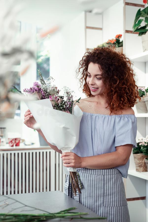 Beaming red-haired florist being amazed with her composed flowers royalty free stock images