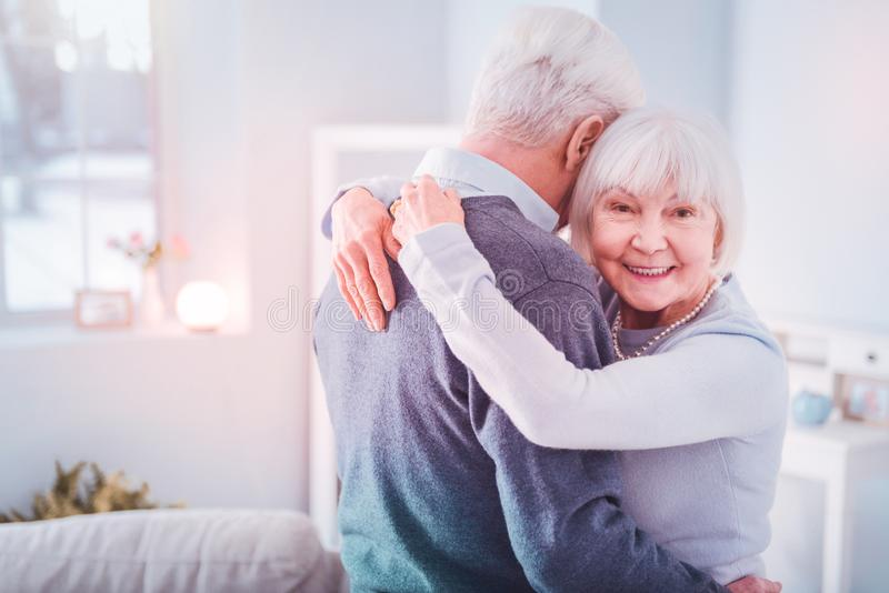 Beaming retired woman feeling happy hugging her grey-haired husband royalty free stock image